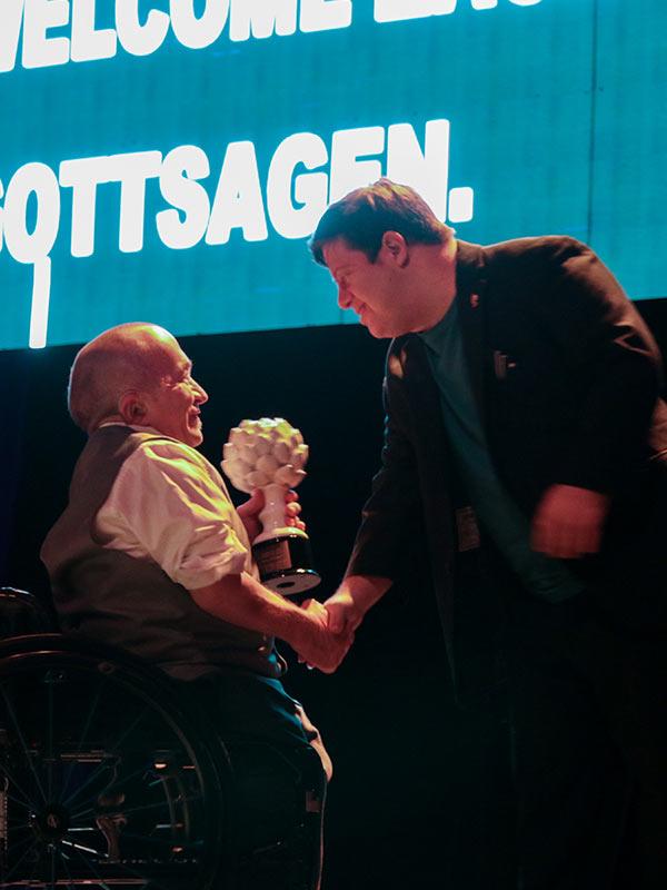 Zack Gottsagen receives a handshake from the host and receives an award.