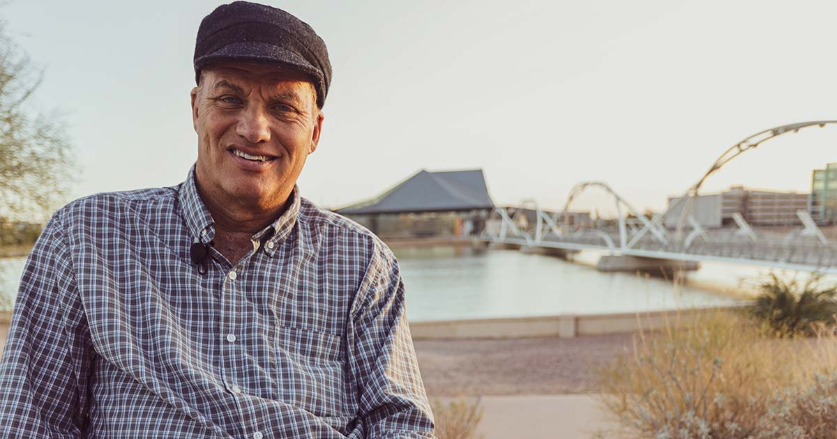 Close up shot of him in front of a bridge in Downtown Tempe. Michael, in his late 40s to early 50s wears a plaid button up shirt.