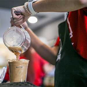 A photo shows the hands of an employee pouring a drink from a blender into a plastic cup.
