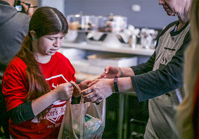 A Spencer's Place employee is handing a plastic bag of food to a customer. The employee, a young woman with brown hair, wears the red t-shirt, black sleeves undernearth the red shirt and has her hair pulled into a ponytail and hanging off her right shoulder.