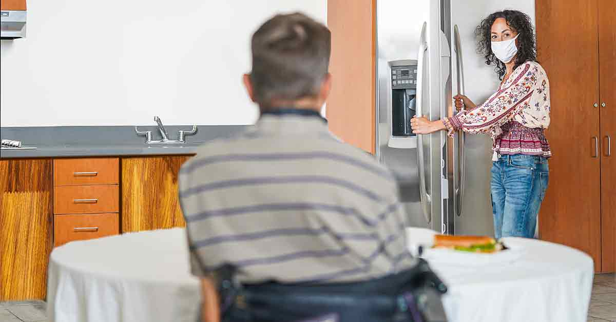 A home care services caregiver preparing food from the refrigerator to serve a person with a disability. Both people are wearing masks.