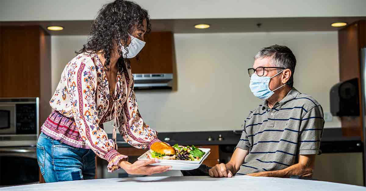A home care services caregiver serves food to a person with a disability. Both people are wearing masks.