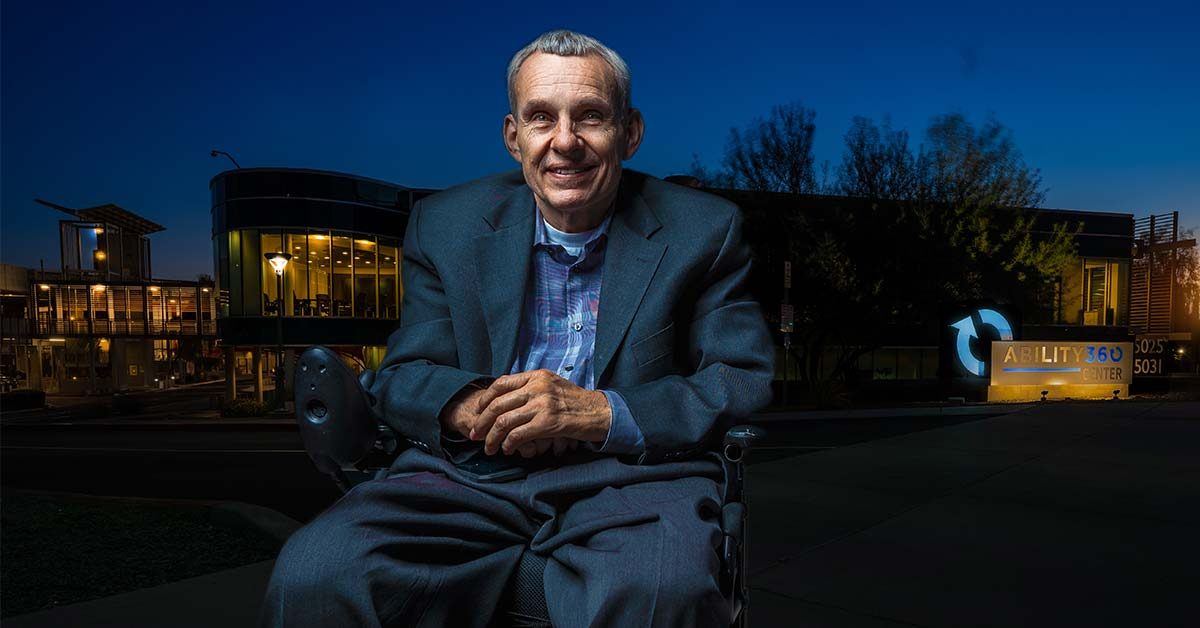 Phil Pangrazio poses for a picture in front of Ability360 at night. Lights illuminate the Sports & Fitness Center in the background.