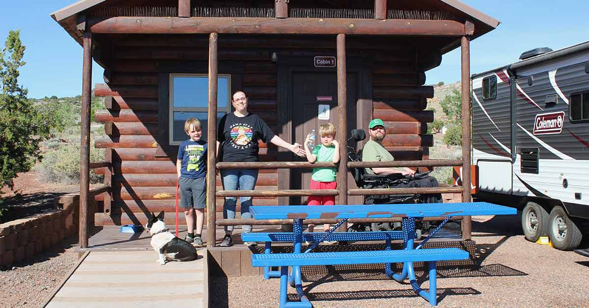 A family poses for a picture on a cabin porch at Lyman Lake State Park. A dog sits on the ramp by which the porch is accessible.