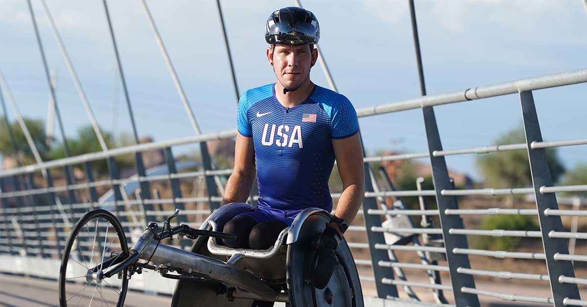 Paralympic athlete Erik Hightower poses for a picture in his Team USA shirt and a helmet.