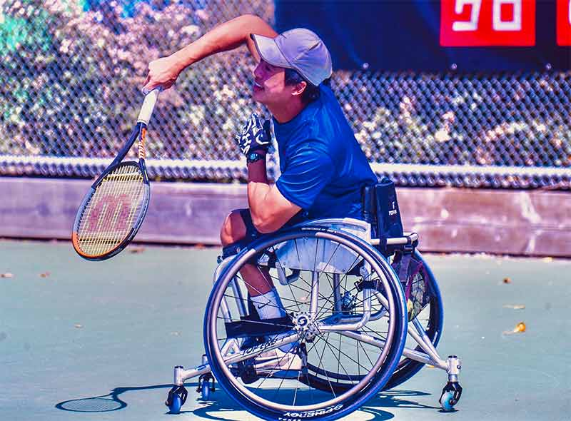 Wheelchair tennis athlete, Jason Keatseangslip bats a tennis ball back toward his opponent, who is not in frame.