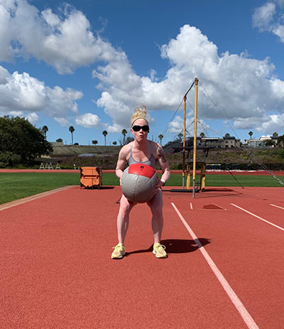 Photo depicts track and field Paralympian Kym Crosby lifting a weighted ball.