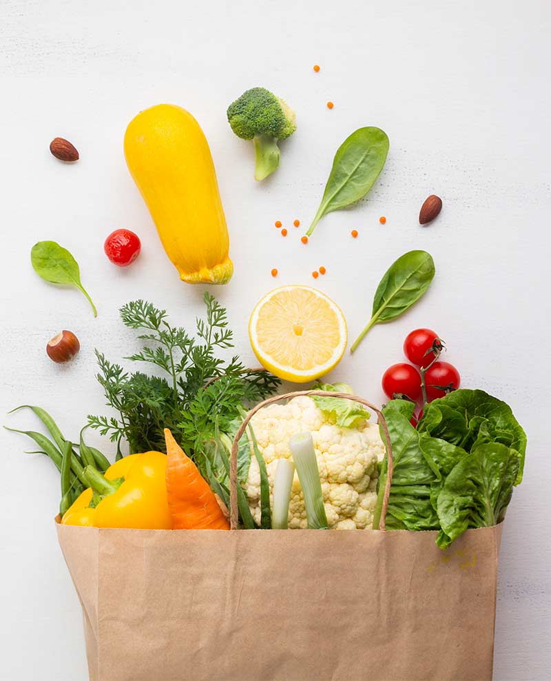 Image depicts a paper bag of vegetables that has been knocked over and the vegetables are spilling out.