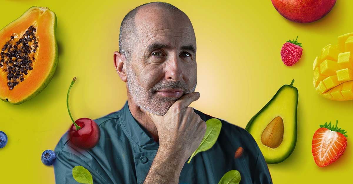 Chef Steve Norton poses in front of a yellow-green background of different fruits.