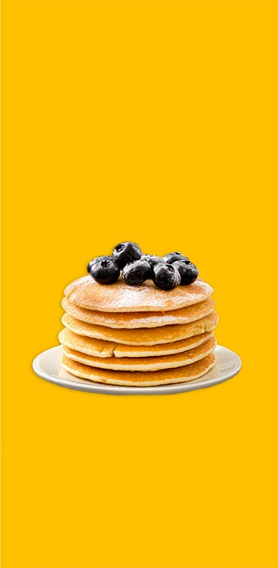 Image depicts a stack of pancakes topped with blueberries against a solid yellow background.