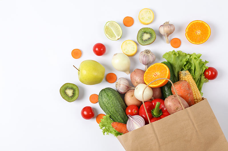 Image depicts a paper grocery bag tipped over with vegetables and fruit falling out of it.