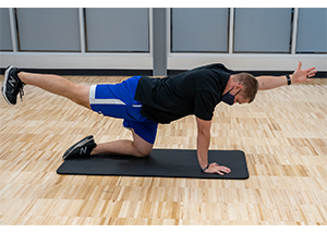Man on his knees, one straight leg raised to 90 degrees even with his back, opposite arm also raised to 90 degrees. Arm, leg and body should make a straight line.