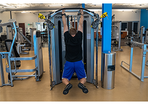 Man hanging from exercise bar. Arms shoulder length apart. Legs slightly bent to avoid hitting the ground.