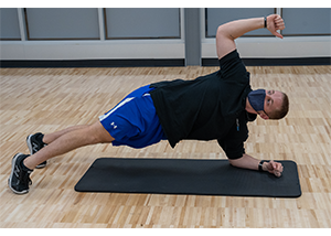 Man on the ground, supporting his weight with both feet, weight distributed on his toes and on one elbow. Twisting so that one arm is in the air. Both elbows and shoulders make a straight line.