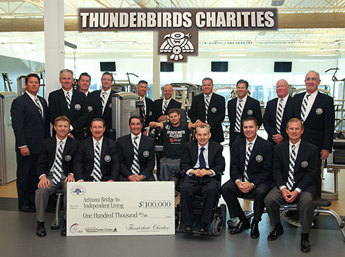 A large group of men stand together in fine suits. Two men in the group use wheelchairs. A large check sets in front of them for $100,000 to A.B.I.L from Thunderbirds Charities.