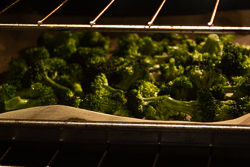 Broccoli florets on a baking sheet in the oven