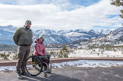 Quinn Brett and co-worker Jesse Miller stand in front the a snow-capped Rocky Mountain National Park mountain range. The two wears cold weather clothing and are both smiling at the camera.