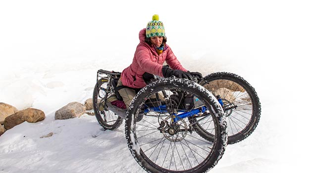 Quinn Brett sits in her custom Bowhead cycle. The three-wheeler is a motorized, off-road capable handcycle.