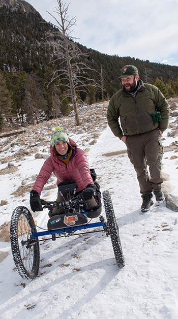 Quinn Brett and her co-worker on a trail in Rocky Mountain National Park. Brett rides her Bowhead bike and Miller walks beside her.