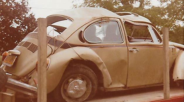 A Volkswagon sitting on a trailer. The vehicle has significant damage to the top of the roof and the side windows.
