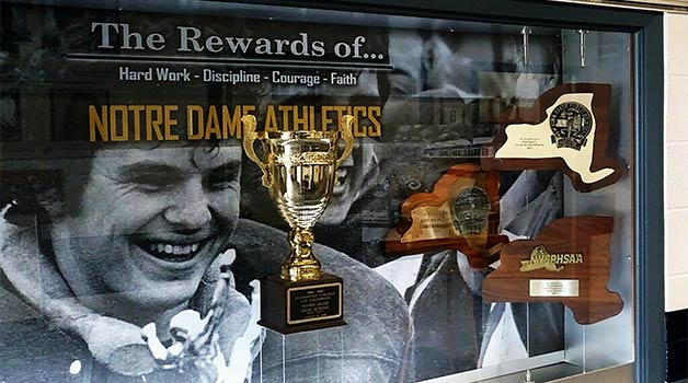 A photo of a gallery of a trophy and plaques from Notre Dame High School. On the back wall of the display is a grayscale photo of a smiling Phil Pangrazio wearing a football uniform.
