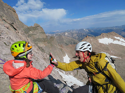 An excited Quinn Brett is shown high-fiving another woman. They both wears winter jackets, gloves, climbing helmets and climbing gear around their torsos.