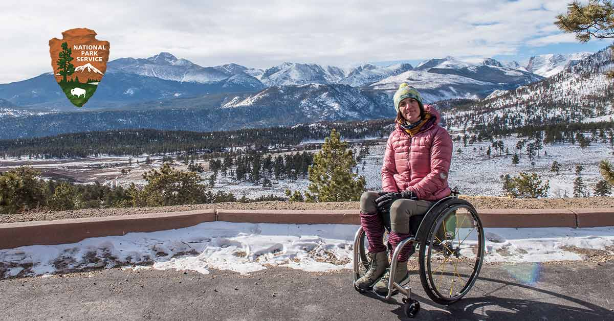 Quinn Brett sits smiling at the camera in her wheelchair with the snow-covered Rocky Mountain National Park behind her.