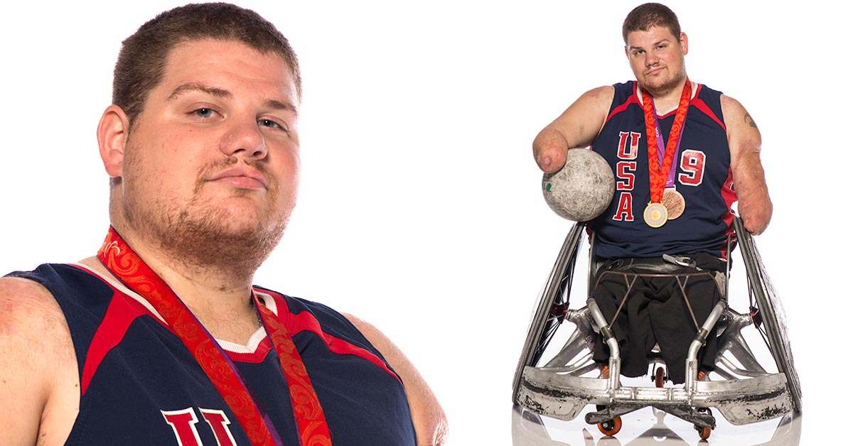 Nick Springer sits in his athletic manual wheelchair holding a rugby ball under one arm. He is wearing a red, white and blue jersey that reads U.S.A. 9. He has two medals hung around his neck.