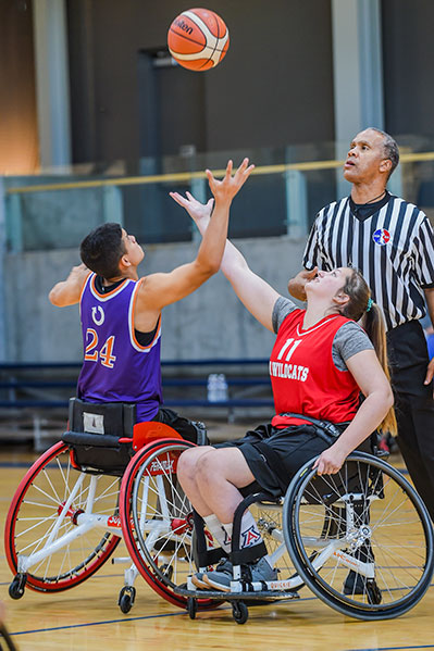 A young boy and girl playing wheelchair basketball. The boy and girl reach their arms up to tap the ball above them. The referee stands to the side of them.