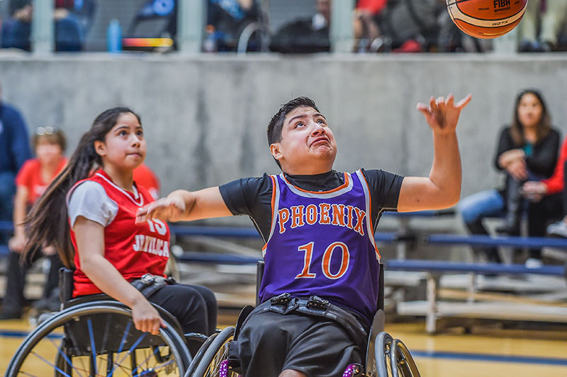 A young boy and girl playing wheelchair basketball. Both look up for the basketball.