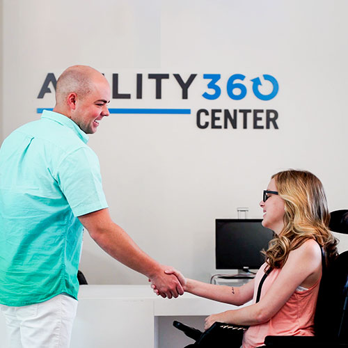 A young man shakes the hand of a young woman. The woman uses a power chair. A sign in the background reads Ability360 Center.